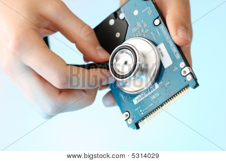 Doctor Holding Stethoscope Against A Back Side Of The Notebook Harddisk