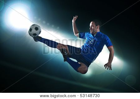 Soccer player in mid air kicking the soccer ball