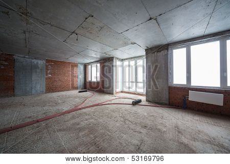 Empty room with brick wall and several radiators