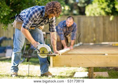 Mid adult carpenter cutting wood with handheld saw while coworker helping him in background at construction site