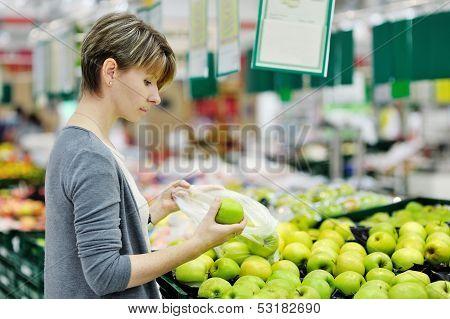 Woman Choosing Apple At Fruit Supermarket