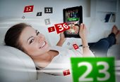 Woman lying on couch and gambling on tablet with holographic numbers around her poster