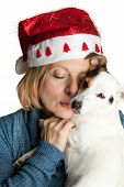 Woman with christmas hat hugging her jack russell. poster