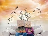 Composite image of silly employees with arms folded wearing boxes on their heads with smiley faces on a couch poster