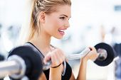 Woman in gym lifting weights poster