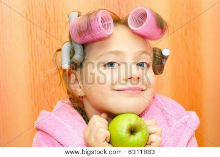 Girl in a pink housecoat with curlers in the head and the apple of her face isolated on orange background. poster