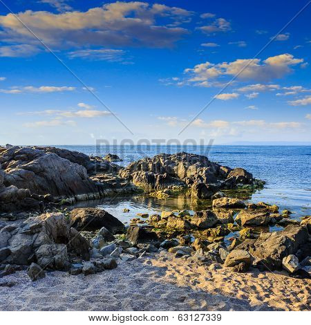 Sea Coast With Boulders And Sand