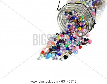 Detail of glass jar of beads on white background for crafts jewelry poster