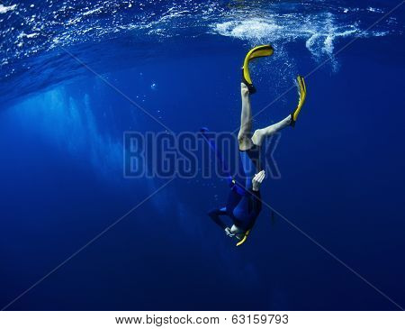 Free diver performing equalization at the beginning of the dive