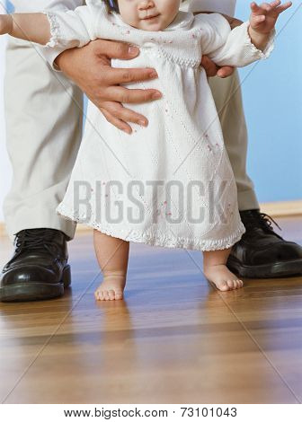Baby girl taking first steps with fathers help