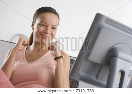 Woman cheering while looking at computer