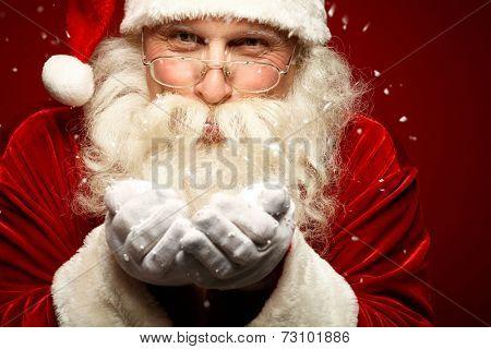 Playful Santa Claus blowing snow and looking at camera
