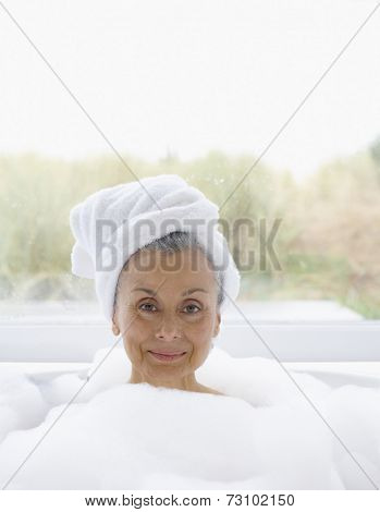 Portrait of elderly woman in bubble bath with towel wrapped around head
