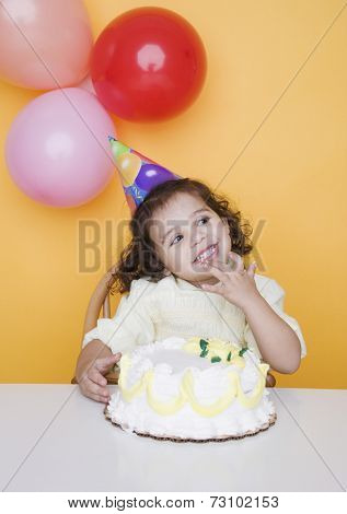 Portrait of young girl with birthday cake