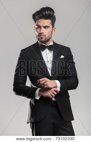 Portrait of a handsome young man wearing a tuxedo, looking away from the camera while ajusting his button.
