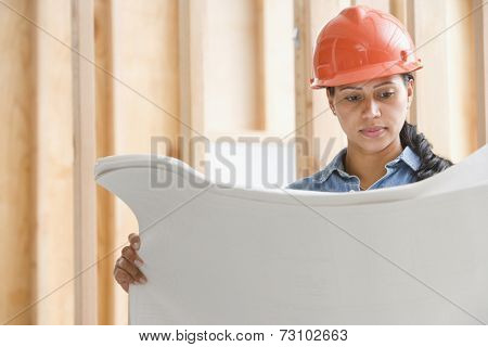 Female construction worker reading plans