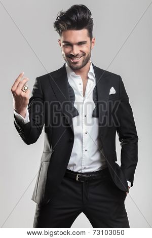 Elegant young man in tuxedo snapping his finger while smiling for the camera, holding one hand in the pocket. On grey background.