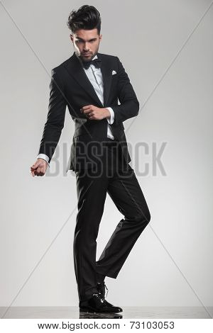 Full length picture of a elegant handsome man snapping his fingers while looking at the camera.