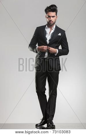 Picture of an elegant young man ajusting his tuxedo while looking at the camera. On grey studio background.