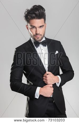 Close up of an elegant young man ajusting his tuxedo while looking at the camera