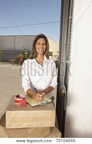 Businesswoman writing on a yellow pad in a garage