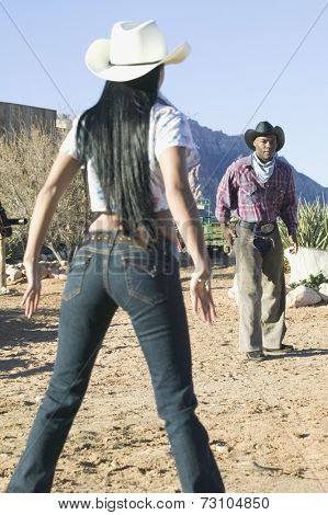 Young couple in cowboy outfits having a shootout