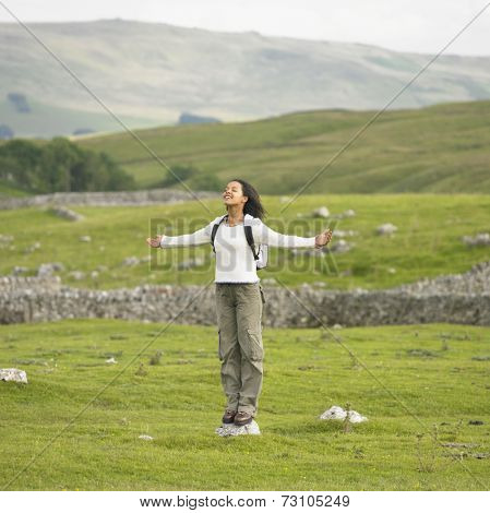 Young woman standing on a rock with her arms outstretched in rural location