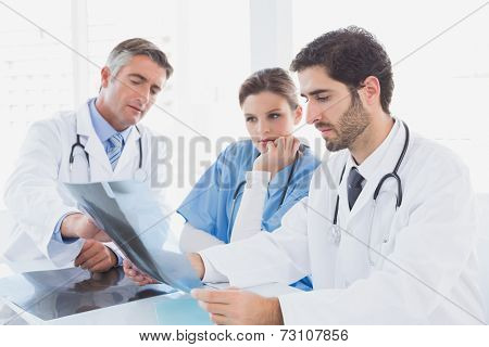 Doctors sitting together with x-rays and discussing resutls