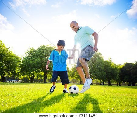 Little boy playing soccer with his father.