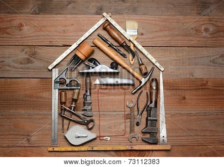 High angle shot of a group of construction tools arranged in the shape of a house. Horizontal format on a rustic wood background.