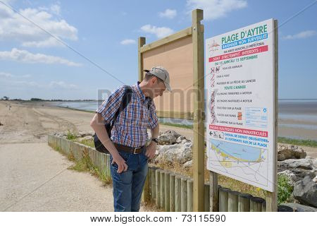 AYTRE, POITOU-CHARENTES, FRANCE - JUNE 25, 2013: Tourist reading the rules at the beach. The beach is flat and shallow, making a good bathing spot for children, and an excellent spot for windsurfing