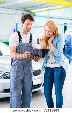 Male workshop mechanic handover car with checklist to client