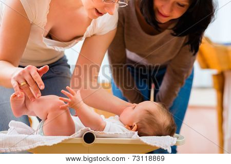 Midwife examining newborn baby at postnatal care in practice checking weight with scale
