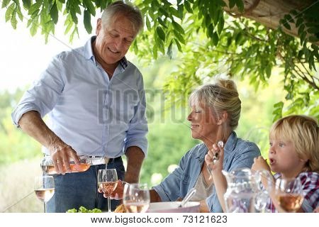 Family having summmer lunch in country house poster
