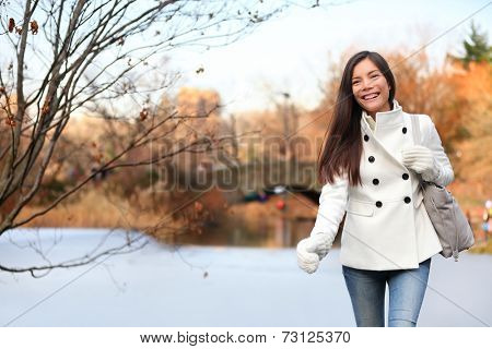 Woman walking happy in Central park, New York City in late fall early winter with skating rink in background. Candid smiling multi-ethnic girl on Manhattan, USA.