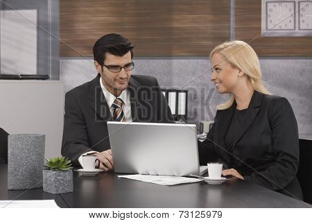 Young businesspeople sitting at table in meetingroom, working with laptop computer, drinking coffee.