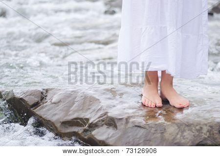 Girl's feet wading in shallow water