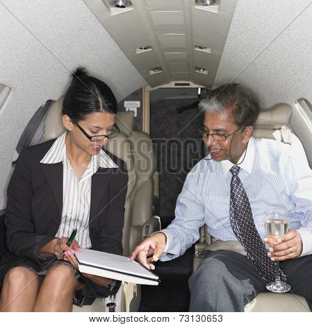 Businesswoman and businessman inside airplane