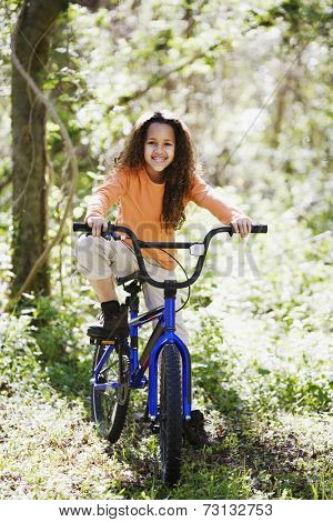 Young girl on bicycle in woods