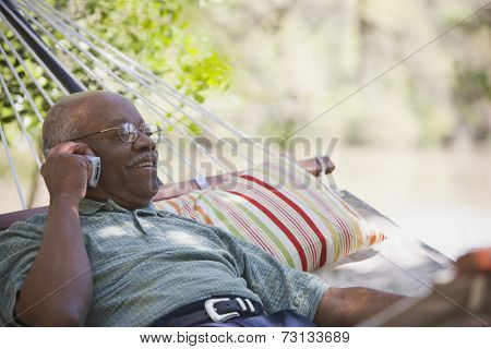 Senior African man using cell phone in hammock