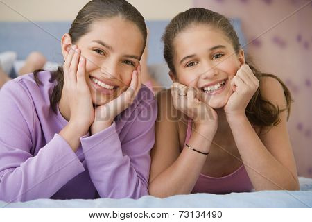 Hispanic sisters laying on bed smiling