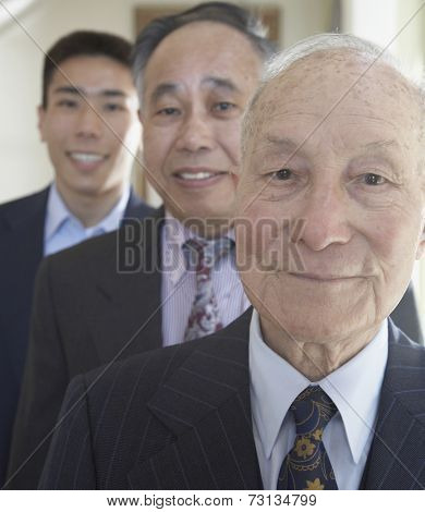 Senior Asian man with family members in background