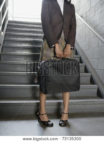 Businesswoman holding briefcase at bottom of stairs