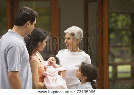 Multi-generational Hispanic family smiling at each other