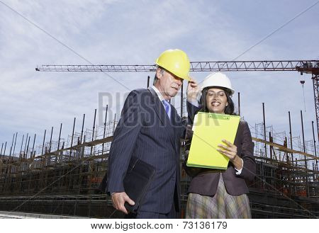 Businesswoman and businessman wearing hard hats at construction site