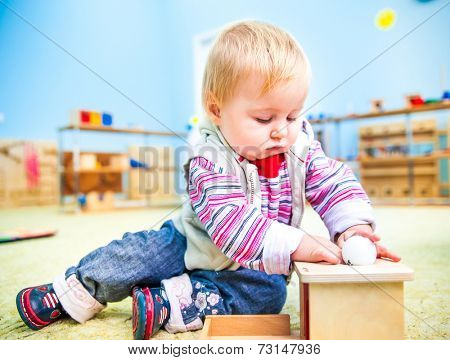 cute little boy in the classroom early development plays with numerous toys