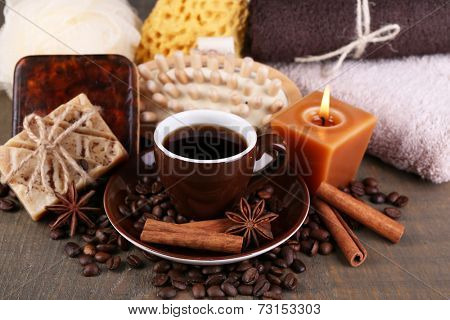 Cup with coffee drink, soap with coffee beans and spices, sponge and massage brush on wooden background. Coffee spa concept poster