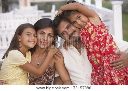 Hispanic family hugging on porch