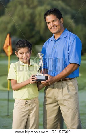 Hispanic father and daughter holding golf trophy