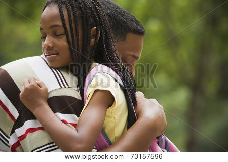 Close up of African father and daughter hugging